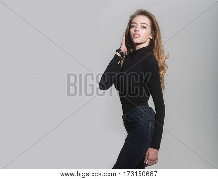 young pretty woman or cute sexy girl with long beautiful curly blonde hair and red lips on adorable face in black jumper and jeans on grey background copy space