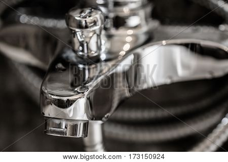Beautiful clean steel chrome metal bathroom or kitchen tap background covered in wet water shiny drops