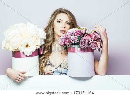 Sexy young pretty woman or cute girl with long hair in floral dress with rose and peony flowers bouquet boxes on lilac background