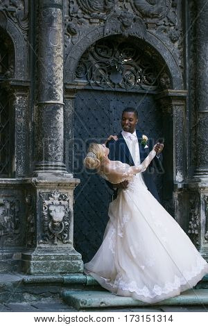 Happy handsome man or african American groom and pretty girl or cute bride with beautiful blond hair in white sexy wedding dress smiling outdoors at ancient building door on grey background