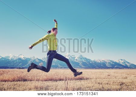 Retro Stylized Picture Of A Happy Young Woman Jumping.