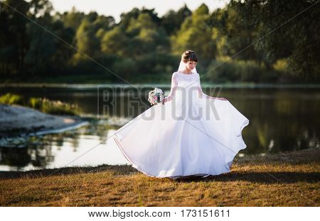 White beautiful long dress. The bride in a white dress on nature background. Wedding photography. Woman in white dress.