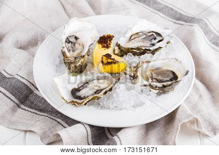 Fresh opened oysters on a plate with lemon slice on a napkin on a wooden table. Selective focus.