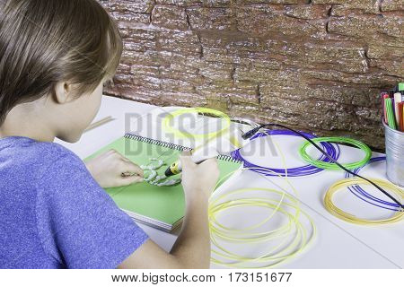 Child using 3D printing pen. Boy making new item. Creative leisure technology education concept