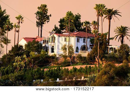Spanish style historic Hacienda Villa surrounded by Palm Trees taken on top of a hill with great views