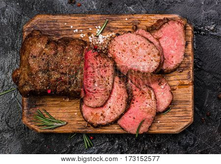 Roast beef on cutting board with salt and pepper. Top view.