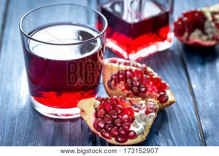 glass bottle of pomegranate juice with fresh slices on blue wooden table background