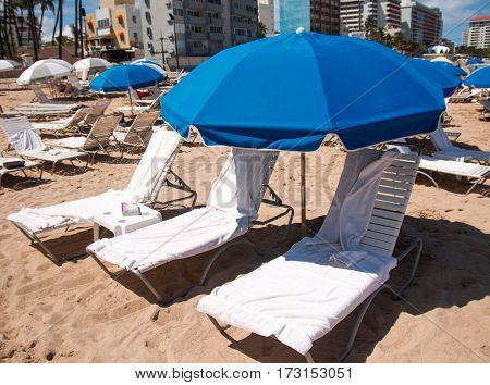 beach chairs and blue unbrellas are set up on a beach in Condado Puerto Rico