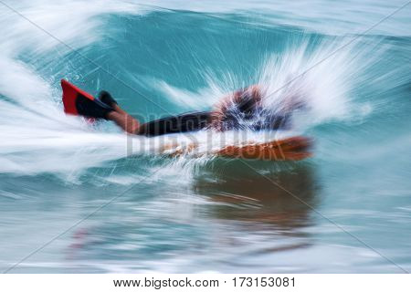 A man boogie boarding in tropical water