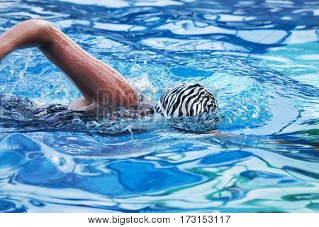 A women swims face down in a very blue pool