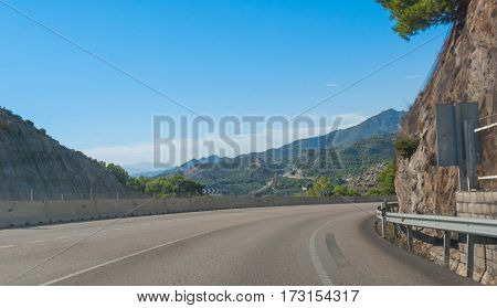 Around the bend - Sunshine on Spanish coastal highway.   Driving view of foothills and mountain ranges on the edges of continental Europe in Spain.