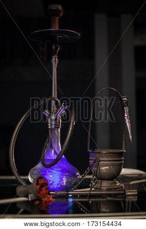 Purple hookah togather with all accessories standing on the table.
