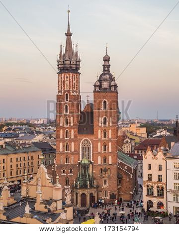 KRAKOW POLAND - 15TH OCTOBER 2016: A high view towards St. Mary's Basilica on Rynek Glowny (Main Square) at sunset. People can be seen.