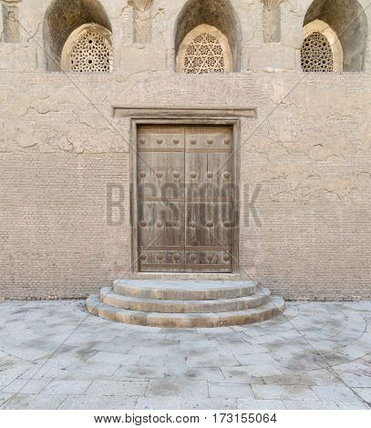 Wooden aged vaulted door threee ornate engraved vaulted windows. three steps and stone wall Medieval Cairo, Egypt