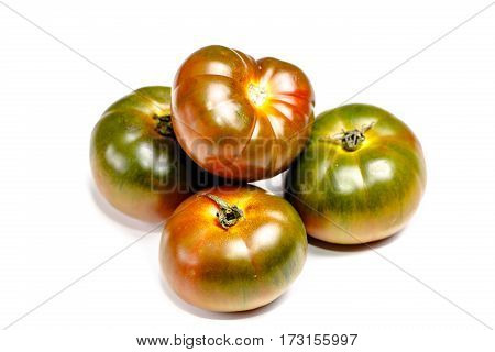 Green, Black Tomato Are On The Board. Isolated.