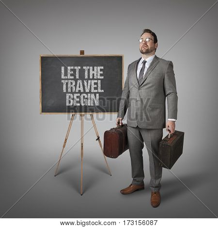 Let the travel Begin text on  blackboard with businessman carrying suitcases