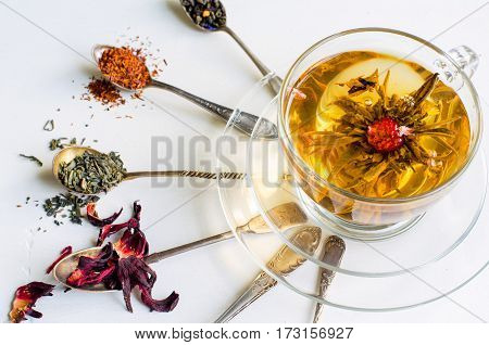 Blooming Or Flowering Tea In A Glass Cup And Silver Spoons With Various Kinds Of Tea On White Backgr