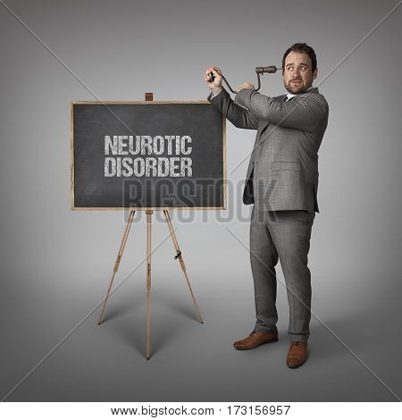 Neurotic disorder text on blackboard with businessman drilling his head