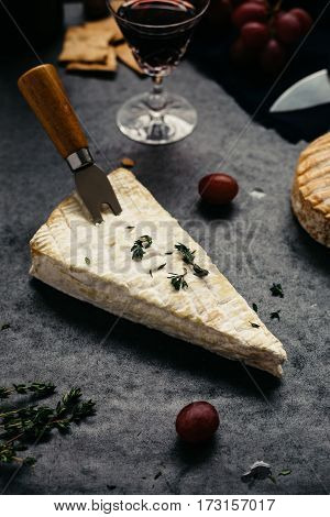 Vertical View of Brie Garnished with Thyme on Rustic Table