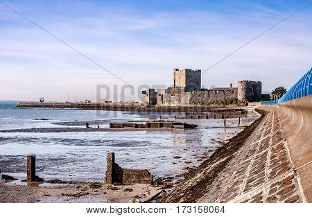 Medieval Norman Castle in Carrickfergus near Belfast Northern Ireland and Belfast Lough during a low tide