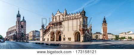 Panorama of Main Market Square (Rynek) in Cracow Poland with the Renaissance Drapers' Hall (Sukiennice) Gothic St Mary church and medieval city hall tower. The biggest medieval market square in Europe