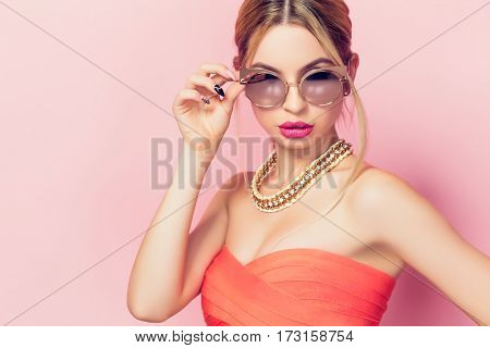 Young woman in bright dress touching the sunglasses on the pink background.