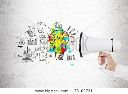 Close up of a hand holding a megaphone near a concrete wall with a bright idea sketch and a business scheme.