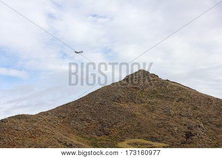 An airplane fly over the peninsula Ponta de Sao Lourenco to the Funchal airport