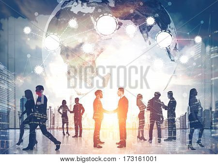 Silhouettes of business people shaking hands and walking against a morning cityscape. There is a world map and a network. Toned image. Double exposure.