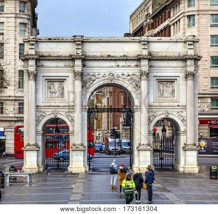 LONDON, ENGLAND - JANUARY 16, 2017 Marble Arch Red Bus Traffic Circle Park Lane London England. Arch created in 1800s by John Nash. Modeled after the Constantine Arch in Rome and Arc D' Triumph in Paris.
