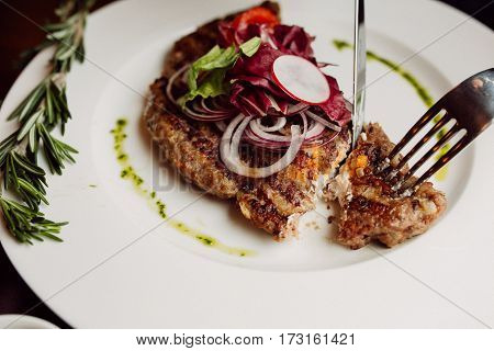 incised cutlet stuffed with soft cheese on white plate Pleskavitsa