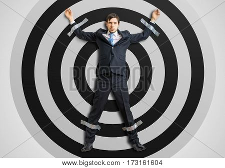 Businessman is taped to the target with adhesive tape.