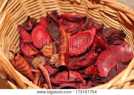 A brown basket full of red potpourri