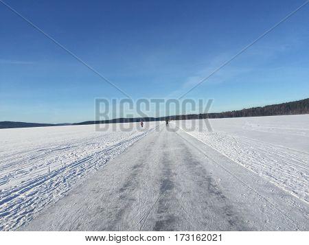 Bild på blåhimmel och fryst sjö täckt med snö och en gångbana