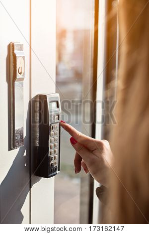 Woman Entering Pin Code To Security System