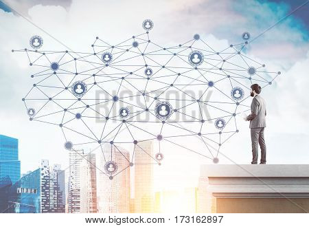 Portrait of a bearded man in a beige suit standing on the roof of a tall building and looking at a giant network sketch in the sky. Toned image.