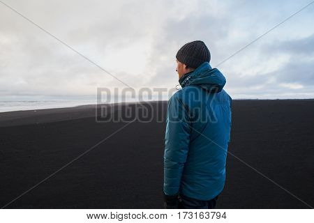 Young man standing on black volcanic beach Iceland.