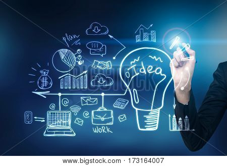 Close up of a hand of a businessman with a blue glowing pen drawing a business sketch and a light bulb on a glassboard. Toned image