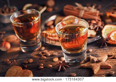Whiskey or liqueur cookies spices and decorations on wooden background. Seasonal holidays concept.