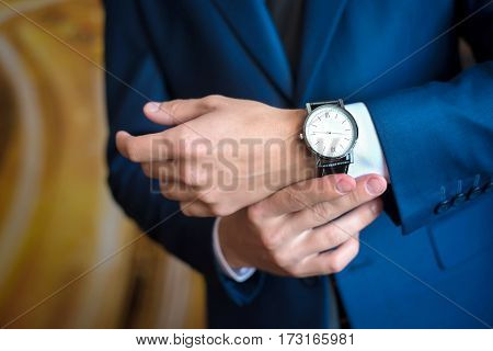 The man in the blue suit looks at his watch, straightens them, hands close up
