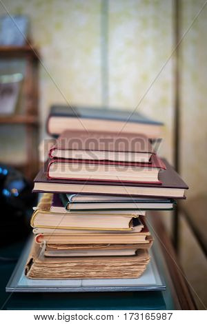 Stack of old battered books on the table.
