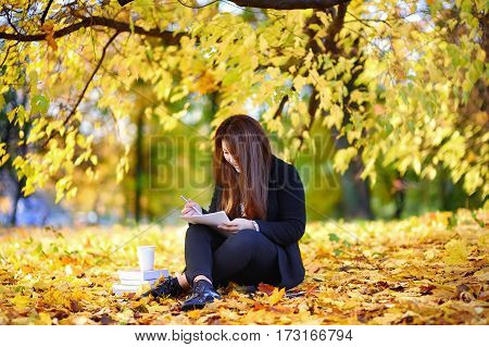Young Asian Woman Studying/working And Enjoying Autumn Day