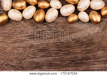 White And Gold Easter Egg Top Border Against A Rustic Wood Background
