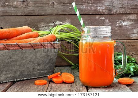 Healthy Carrot Juice In A Mason Jar Glass With Vintage Tray Of Carrots Over A Wood Background