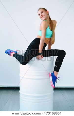Fitness Girl Sitting On A Stretched White Barrel