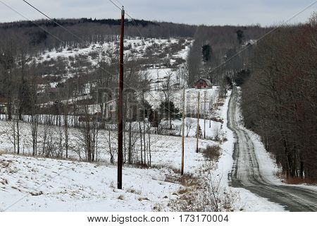 A barn and road with powerlines on a snowy landscape.