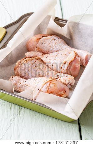 Raw chicken leg on plate at white wooden table