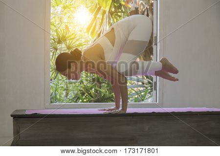 Asian trainee strong woman practicing difficult yoga pose in a nature background