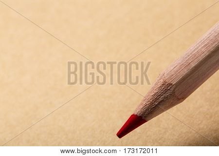 Brown notebook, top view. Wooden red pencil writing on tne brown paper. School and education. Student. Writing instruments.