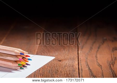 Multicolored pensils on the white paper on a wooden table. Back to school. Copy space. Bunch of the colorful pencils. Brown background. Drawing and painting. Art and design.